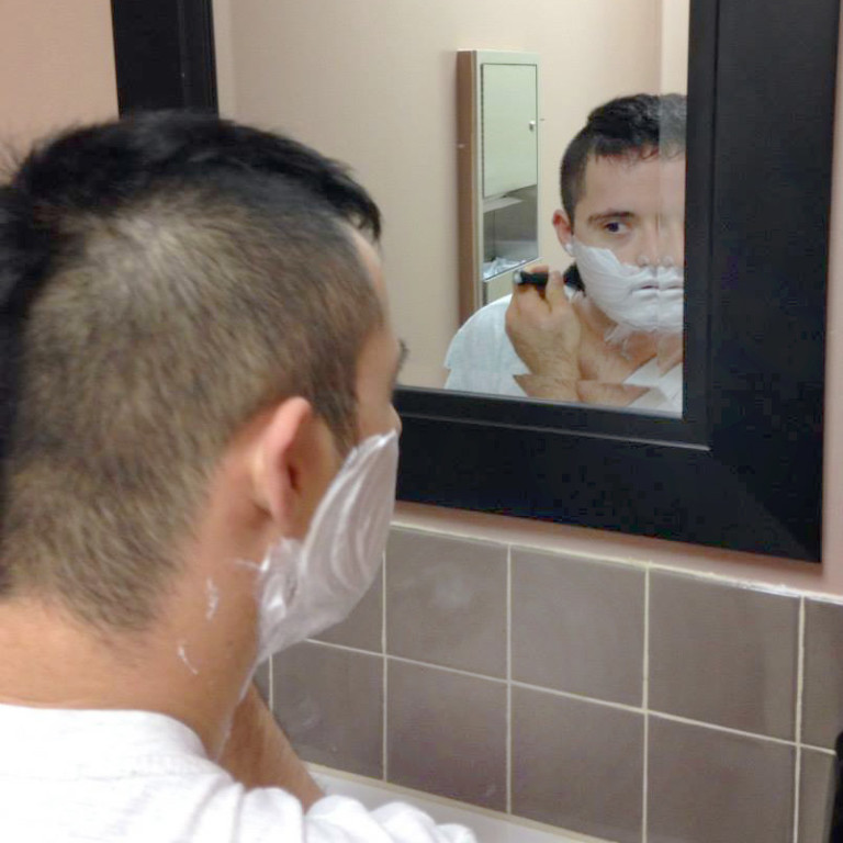 A client practicing activities of daily living by shaving